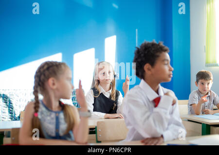 group of school children all raising their hands in the air to answer - Stock Photo