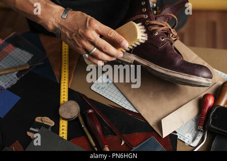 Care for leather shoes with polishing brush. - Stock Photo