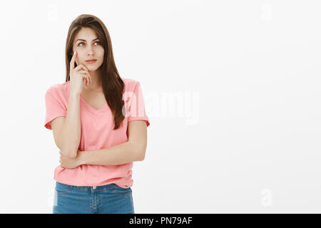 Determined smart attractive female student in pink t-shirt, holding index finger on temple and smiling while gazing at upper right corner, dreaming or making up ideas about future summer vacation - Stock Photo