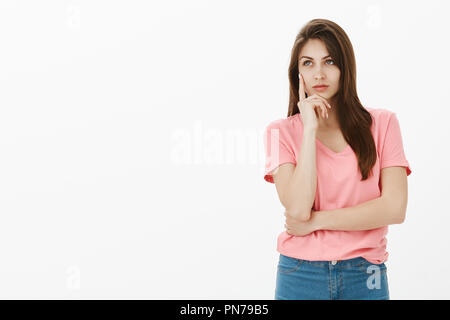 Girl visiting art museum having no clue what painting mean. Dreamy attractive and confident young woman in pink t-shirt, holding palm on cheek and gazing at upper left corner with slight smile - Stock Photo