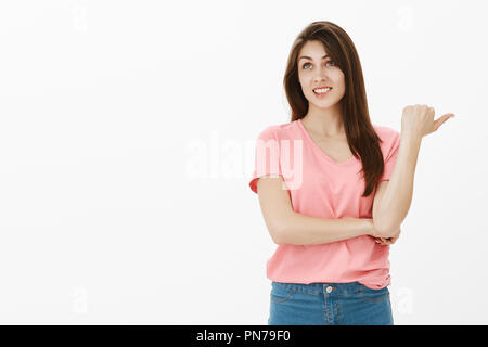 Studio shot of shocked happy young woman talking about something unimpressive, expressing careless opinion about new concept coworker suggested during meeting, smiling and looking up with indifference - Stock Photo