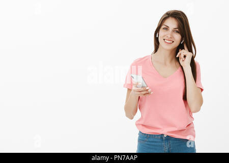 Hi how can I help you. Good-looking friendly and happy female office manager in pink t-shirt smiling broadly while touching wireless earphone in ear and holding smartphone, calling customer - Stock Photo