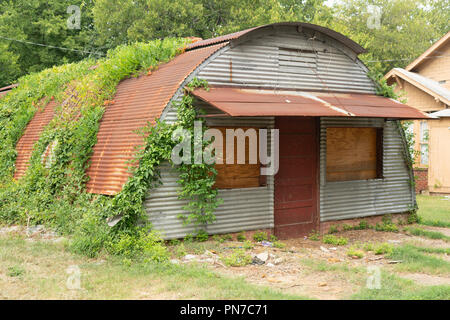 The windows are gone boarded up in this primitive rusty metal shed - Stock Photo