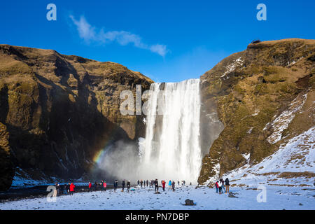 Tourists and rainbow at spectacular Skogar waterfall - Skogarfoss - in South Iceland with gushing glacial melting waters - Stock Photo