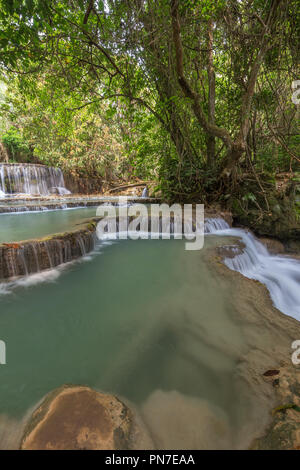 Beautiful view of a small waterfall and cascades at the Tat Kuang Si Waterfalls near Luang Prabang in Laos on a sunny day. - Stock Photo