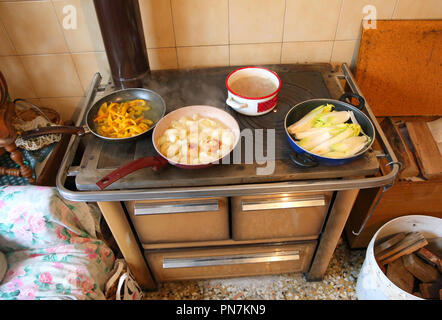 many pots on the wood burning stove in the kitchen of an old house - Stock Photo