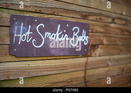 A slate sign that reads 'Hot Smokin Baths' - Stock Photo
