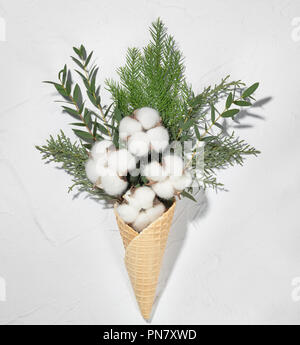 Wafer cone with cotton and fir branch on white background - Stock Photo