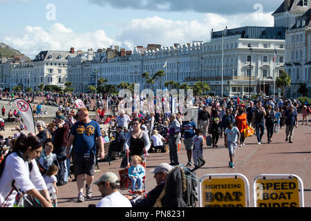 Hundreds of holiday makers enjoying the warm weather on the north shore promenade in Llandudno, North Wales - Stock Photo