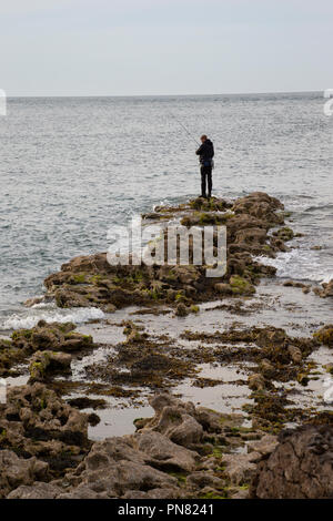 Lone fisherman with rod fishing off rocks on the seashore in Anglesey North Wales. - Stock Photo