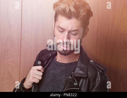 Portrait of a stylish handsome man in a leather jacket - Stock Photo