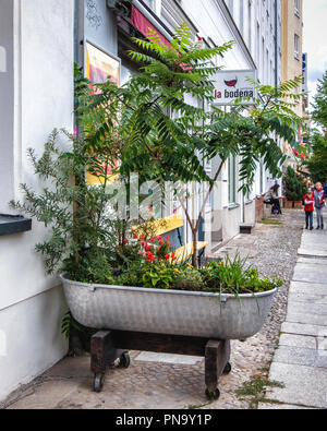 Berlin-Mitte. La Bodega convienience store with plants in old bathtub on pavement - Stock Photo