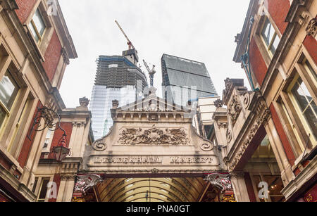Entrance of historic Leadenhall Market with iconic Cheesegrater skyscraper and 22 Bishopsgate partially glazed under construction, City of London EC3 - Stock Photo
