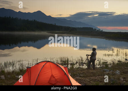 Photographer taking a picture of beautiful lake and mountain near orange tent. - Stock Photo