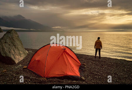 Hiker looking at beautiful lake at sunrise near orange tent. - Stock Photo