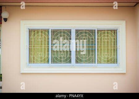 Window with wrought iron to prevent theft. Newly built house with window burglar bars and can see the decorated curtain through the window glass. - Stock Photo