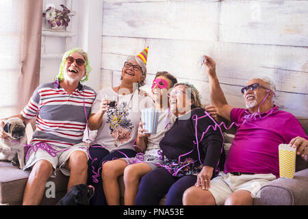 Mixed ages caucasian family at home celebrating an event or party together having a lot of fun. laughs and smiles for happy senior adult and young tee - Stock Photo