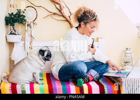 beutiful caucasian woman and funny old pug dog sitting on a bench in the terrace at home working or doing onine shopping with a laptop together. frien - Stock Photo