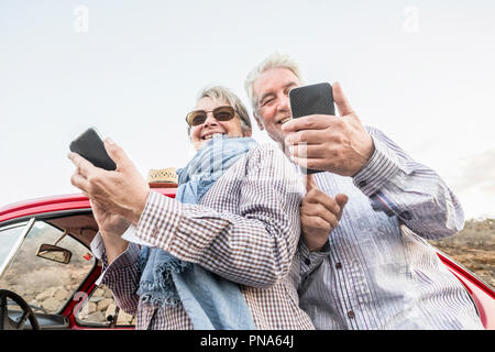 alternative point of view from the bottom for youthful senior couple caucasian people using smartphone to take pictures and connect to internet. trave - Stock Photo