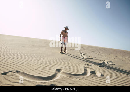 lost in happiness in the middle of the desert with sand dunes. young happy boy teenager enjoying vacation at the beach. clear blue sky in background.  - Stock Photo
