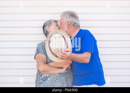 Valentine's day concept with elderly beautiful senior couple kissing hidding with a beige hat with a white wood background wall behind them. love and  - Stock Photo