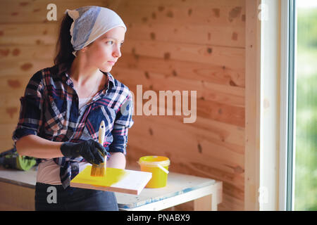 Woman with brush repair in a wooden house - Stock Photo