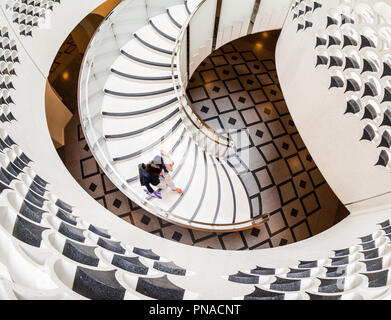 View from above of woman walking down spiral staircase at the Tate Modern in London - Stock Photo