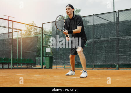 Distant plan of young attractive man playing tennis at tennis court. Player holding outfit in both hands to straighten strike. Athlete is making facia - Stock Photo