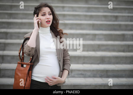 Pregnant woman talking on the phone in the street - Stock Photo