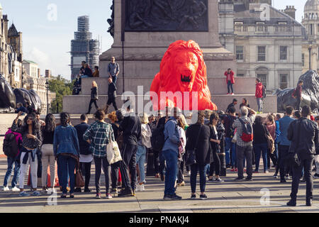 19 September 2018 - London, England. Tourists looking at bright red, poem-roaring lion, recently unveiled in Trafalgar Square. - Stock Photo