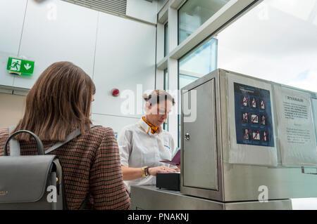 Ryanair operative checks boarding pass and passport at Dublin Airport before passenger boards flight - Stock Photo