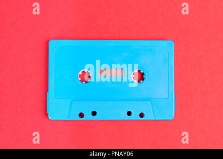 Retro blue audio cassette tape on red paper background - Stock Photo