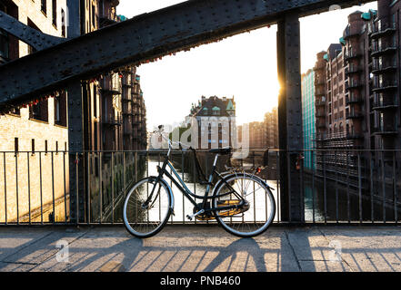 bicycle parked on bridge above water aganst Hamburg cityscape - Stock Photo