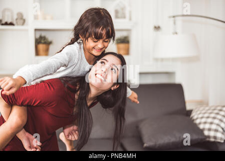 Mother and daughter doing piggyback in funny gesture emotion at home. Young sister playing with girl in good relationship lifestyles relaxation. Happy - Stock Photo