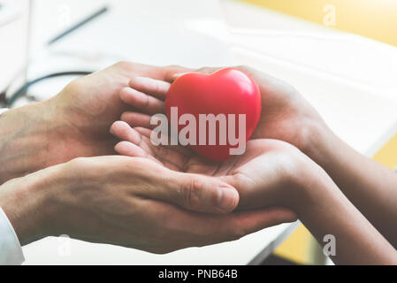 Doctor hands holding and giving red massage heart to patient little children for recover from sickness. Hospital and Healthcare concept. CPR and cardi - Stock Photo