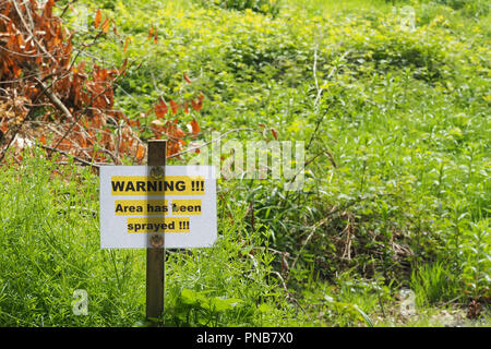 Warning sign alongside River Suir in Cahir, Co. Tipperary, Ireland alerting visitors that pesticide or herbecide has been sprayed on the vegetation. - Stock Photo