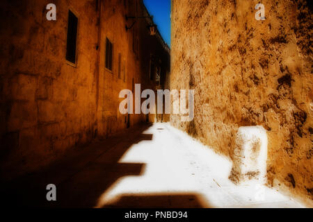 A typical and historical narrow road in Mdina, Malta under a hot blazing sunlight. - Stock Photo