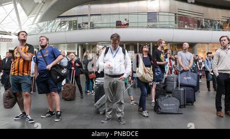 passengers looking at train departure board, Kings Cross railway station, London, England, UK - Stock Photo