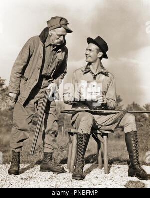 1930s 1940s OLD HUNTER HOLDING SHOTGUN SPEAKING TO SMILING YOUNGER MAN READING STRAIGHT SHOOTING INSTRUCTIONS HOLDING 22 RIFLE - a993 HAR001 HARS OLD TIME NOSTALGIA SHOOTING OLD FASHION 1 STYLE COMMUNICATION SAFETY INFORMATION SHOTGUN PLEASED JOY LIFESTYLE ELDER RURAL COPY SPACE FRIENDSHIP FULL-LENGTH PERSONS RIFLE CARING MALES HUNTER CONFIDENCE SENIOR MAN SENIOR ADULT B&W OLDSTERS CHEERFUL OLDSTER CANVAS LEISURE MANUAL STYLES WISDOM KNOWLEDGE LEADERSHIP RECREATION DIRECTION TO AUTHORITY SMILES ELDERS INSTRUCTING CONCEPTUAL BOOKLET FELT INSTRUCTIONS JOYFUL STYLISH SUPPORT 22 FASHIONS FIREARM - Stock Photo