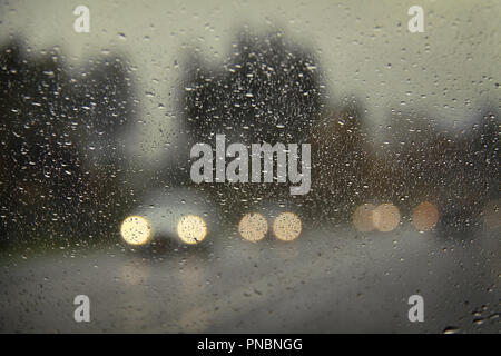 Cars with headlights on viewed through a raindrop-covered windshield. - Stock Photo