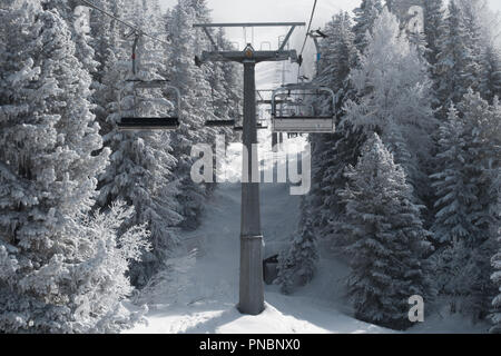 Ski lift under the mist, fog, cables and trees in the mountains - Stock Photo