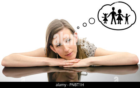 Portrait of a thoughtful young woman leaning on a table, dreaming about  motherhood and family. - Stock Photo