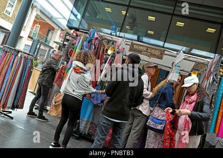 People shopping for scarves at a scarf stall 'Kashimi Scarves' in Spitalfields Market near Brick Lane in East London E1 UK  KATHY DEWITT - Stock Photo