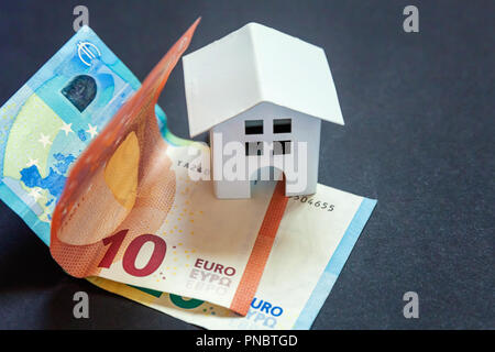 Euro banknotes and symbolic small toy house. Buying property and mortgage - Stock Photo