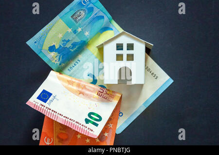 Euro banknotes, and symbolic small toy house. Buying property and mortgage - Stock Photo
