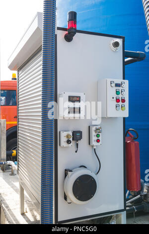 White apparatus at a gas station with numbers and buttons - Stock Photo