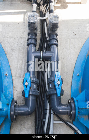 Black communication pipes with valves and black hoses - Stock Photo