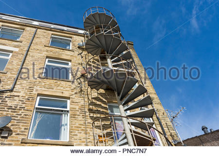 A metal spiral staircase for escape in case of fire on a block of flats in Sandylands, Morecambe, Lancashire - Stock Photo
