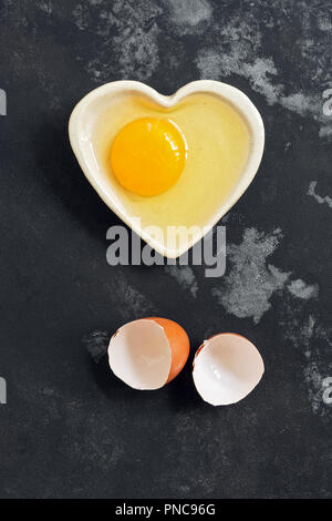Raw egg broken in a bowl and eggshell on a dark concrete background. Flat lay. - Stock Photo
