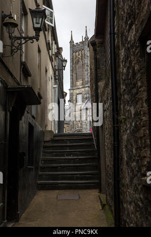 Kilkenny, Republic of Ireland - August 14th 2018: Looking up an alleyway towards the tower of the St. Mary's Medieval Mile Museum in the historic city - Stock Photo